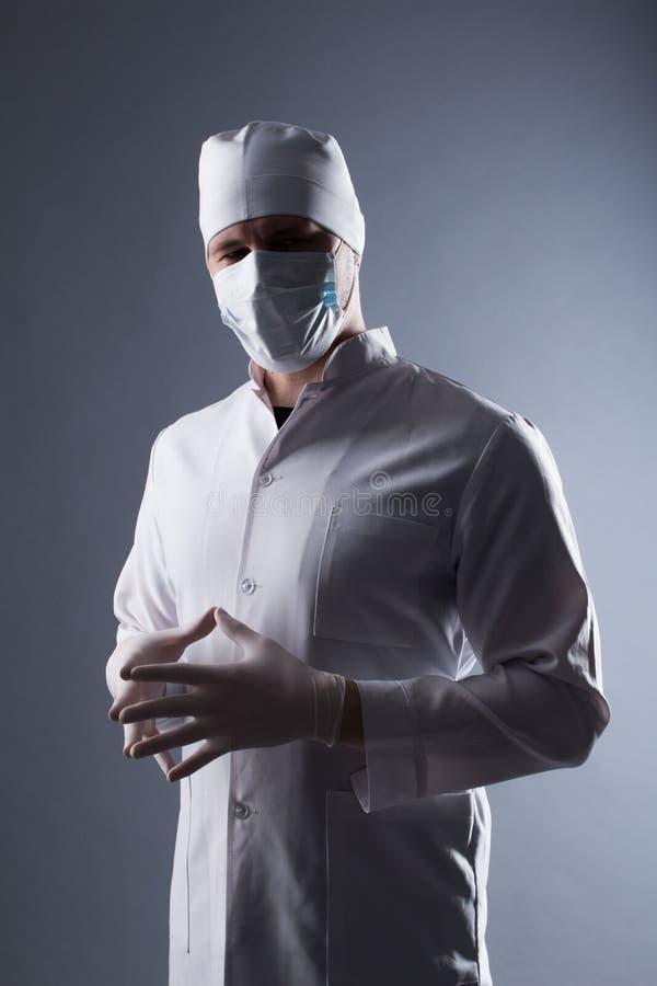 El doctor de sexo masculino en casquillo y la máscara llevan los guantes médicos de goma adentro contra imagenes de archivo