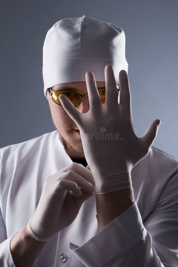 El doctor de sexo masculino en casquillo y los vidrios llevan los guantes médicos de goma en estafa fotos de archivo libres de regalías