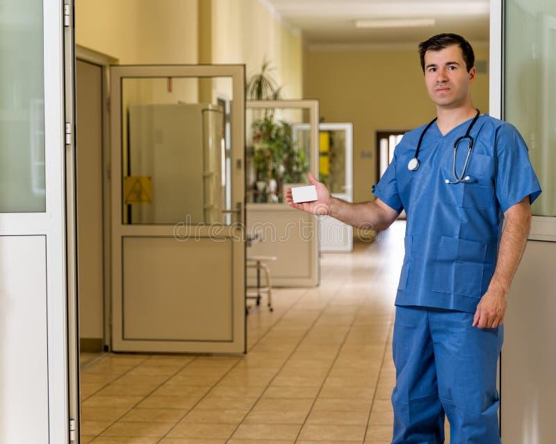 El doctor de sexo masculino de la Edad Media en azul friega con el estetoscopio que sostiene la tarjeta blanca imagen de archivo