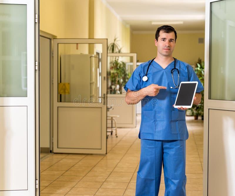 El doctor de sexo masculino de la Edad Media en azul friega sostenerse y señalar para esconder la tableta foto de archivo libre de regalías