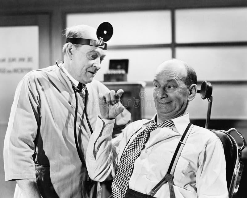 El doctor de sexo masculino que escucha un hombre que esté explicando algo con sus fingeres (todas las personas representadas no  imágenes de archivo libres de regalías