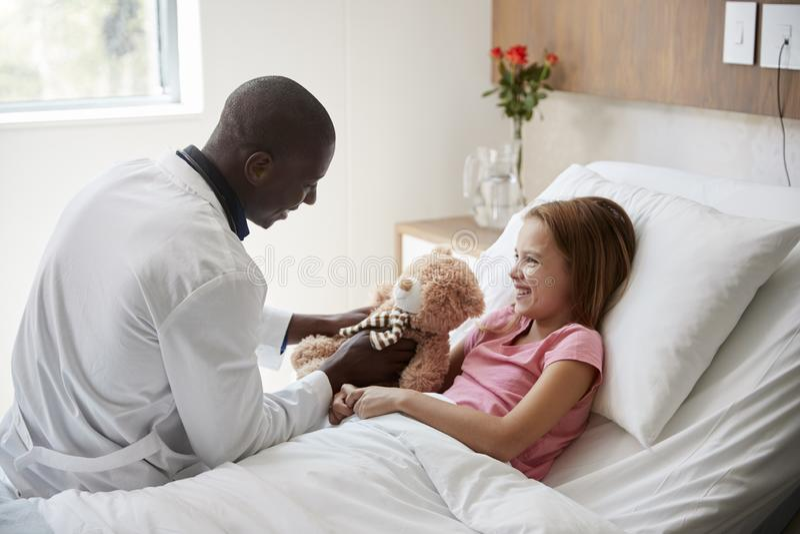 El doctor de sexo masculino Visiting Girl Lying en la cama de hospital que abraza a Teddy Bear fotos de archivo