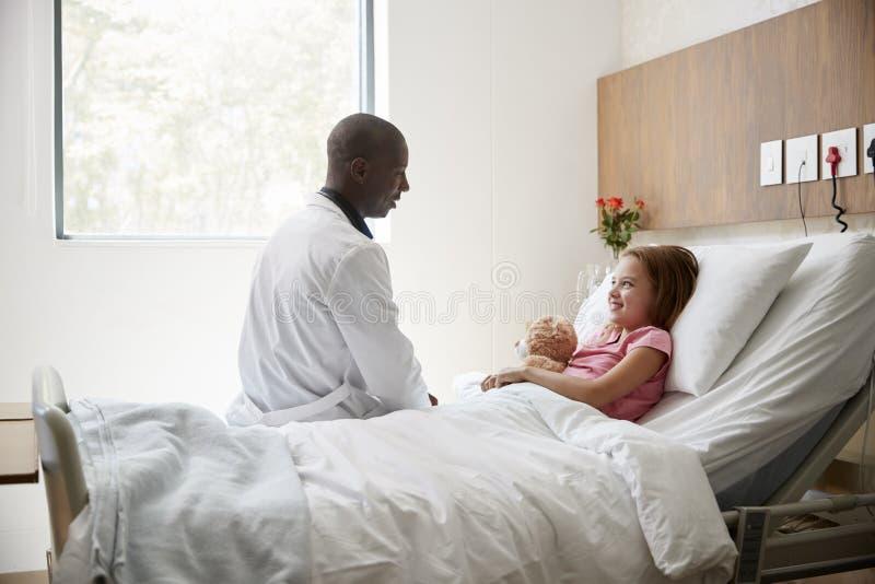 El doctor de sexo masculino Visiting Girl Lying en la cama de hospital que abraza a Teddy Bear fotografía de archivo libre de regalías