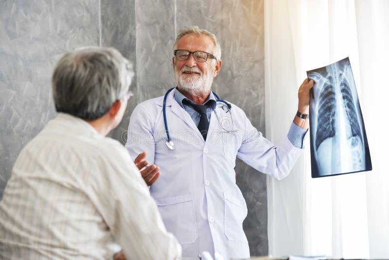 El doctor de sexo masculino y el paciente asiático están examinando la película de radiografía juntos fotografía de archivo libre de regalías