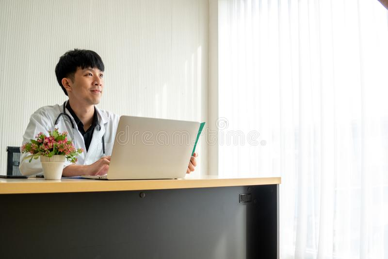 El doctor del hombre joven está leyendo la carta paciente y se siente confiado en su pensamiento en su escritorio de trabajo imagen de archivo libre de regalías