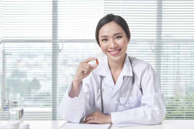 El doctor del médico especialista del hospital muestra la píldora para llevar su paciente imagen de archivo