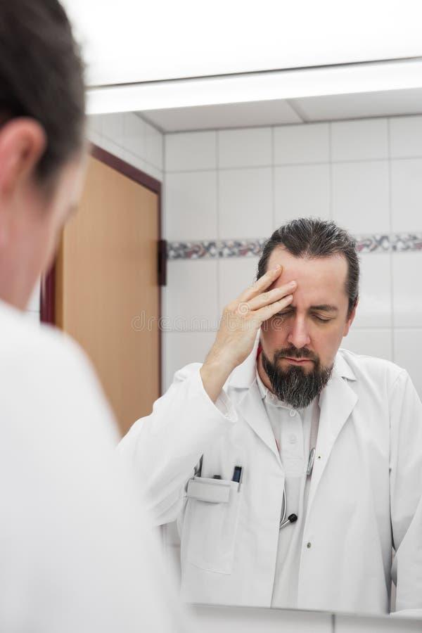 El doctor delante de un espejo tiene dolor de cabeza fotografía de archivo