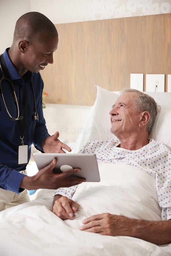 El doctor With Digital Tablet que visita y que habla con el paciente masculino mayor en cama de hospital imagenes de archivo