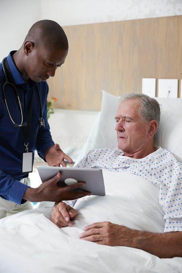 El doctor With Digital Tablet que visita y que habla con el paciente masculino mayor en cama de hospital fotografía de archivo