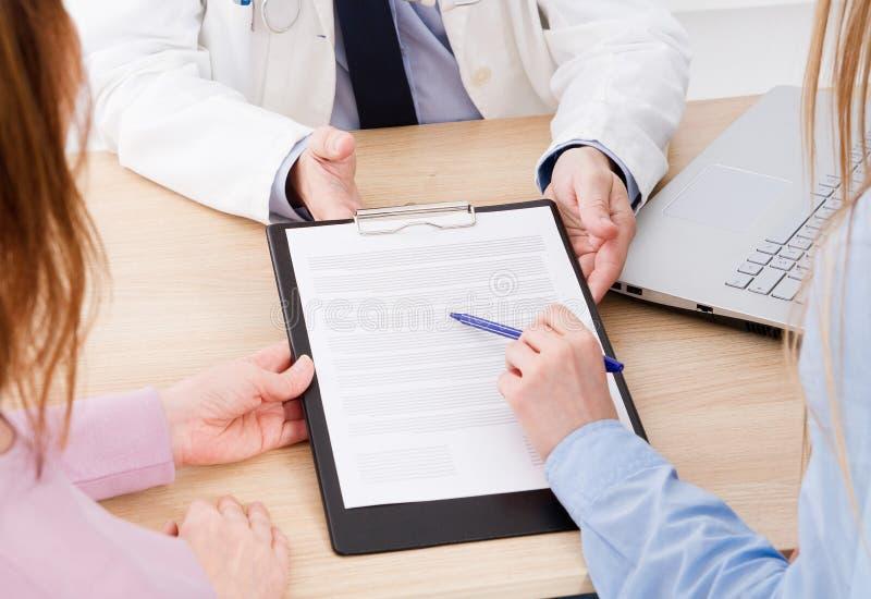 El doctor discute con el contrato médico en la clínica, m de los pacientes fotos de archivo