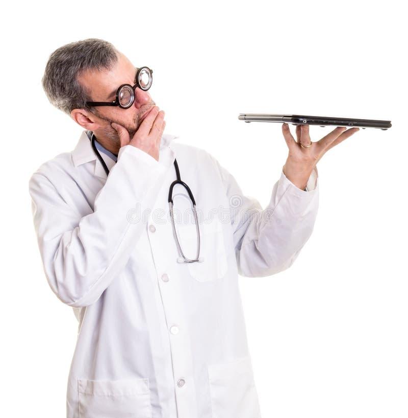 El doctor divertido Examines un ordenador portátil imagen de archivo libre de regalías