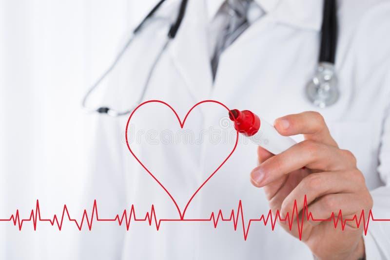 El doctor Drawing Heart Symbol cerca del electrocardiograma fotografía de archivo