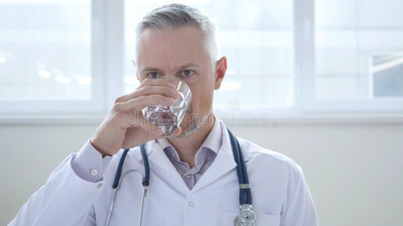 El doctor Drinking Water en clínica imagen de archivo libre de regalías