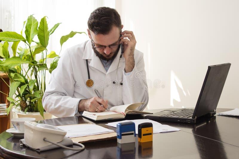 El doctor durante una llamada de teléfono ahorra la cita en el calendario imagenes de archivo