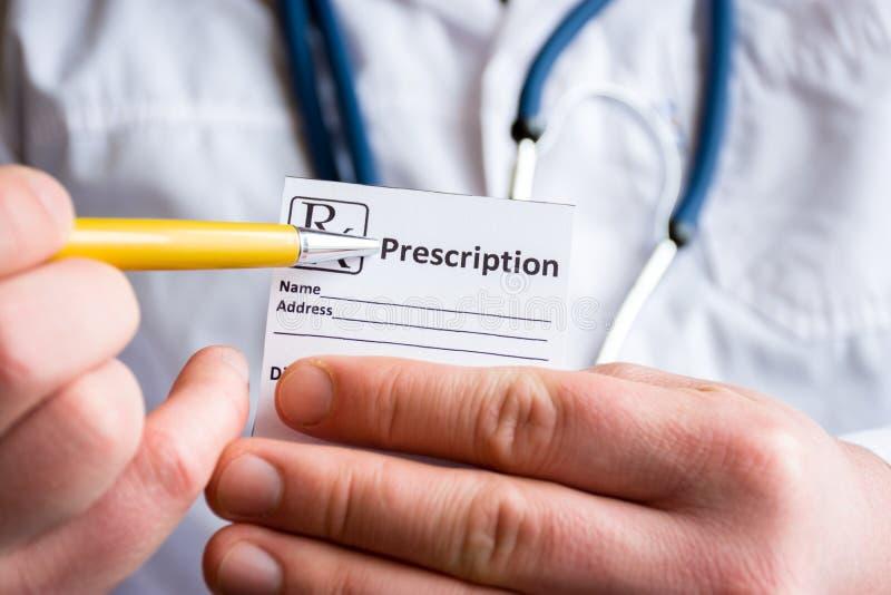 El doctor en el primero plano que sostiene la muestra de prescripción o de receta para la droga, la otra mano indica la designaci fotos de archivo