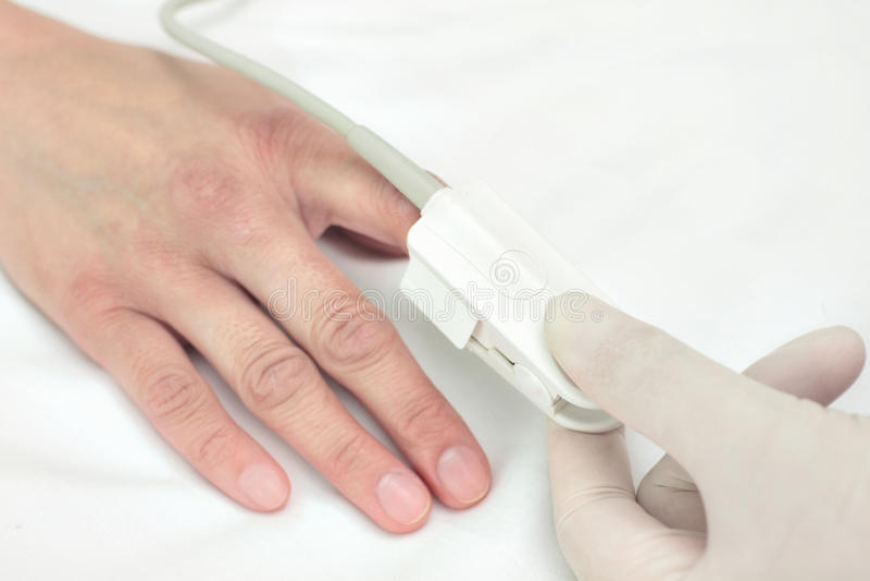 El doctor en un guante pone el sensor en el finger del paciente. Símbolo de foto de archivo libre de regalías