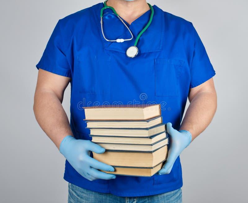 el doctor en uniforme azul y guantes estéril del látex sostiene una pila de libros en su mano foto de archivo