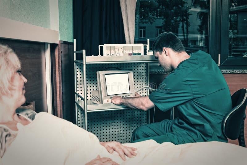El doctor en uniforme está mirando el monitor del aparato médico mientras que imágenes de archivo libres de regalías