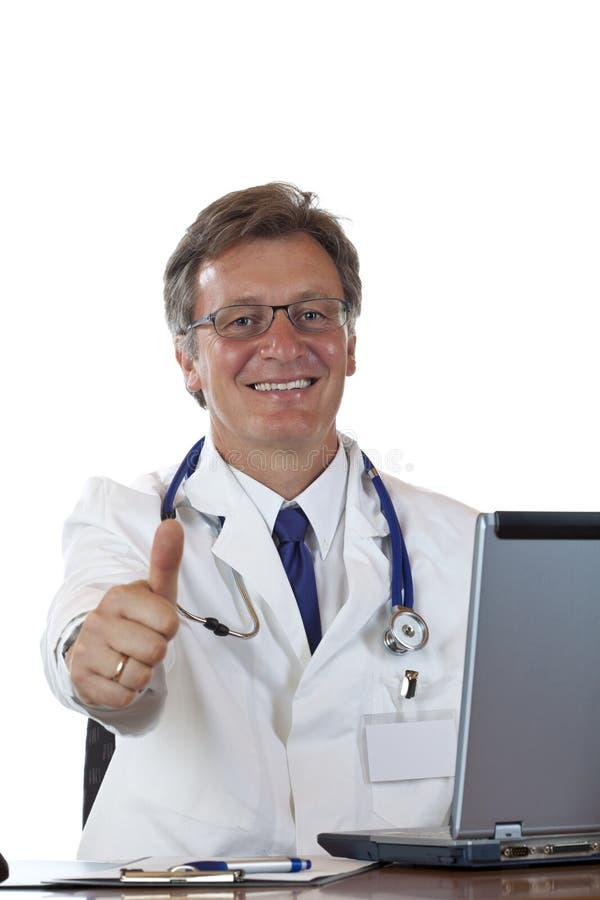 El doctor envejecido acertado en el escritorio detiene el pulgar foto de archivo libre de regalías