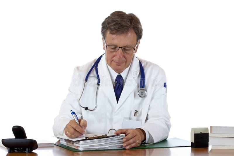 El doctor envejecido anota informe médico foto de archivo