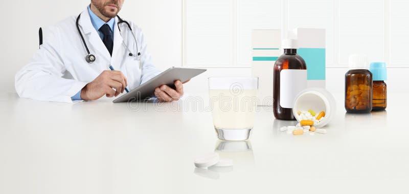 El doctor escribe la prescripción médica con la tableta digital en una oficina del escritorio con la curación del vidrio, de aspi imagenes de archivo