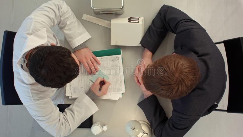 El doctor escribe el valor al paciente con precio grande Visión superior foto de archivo