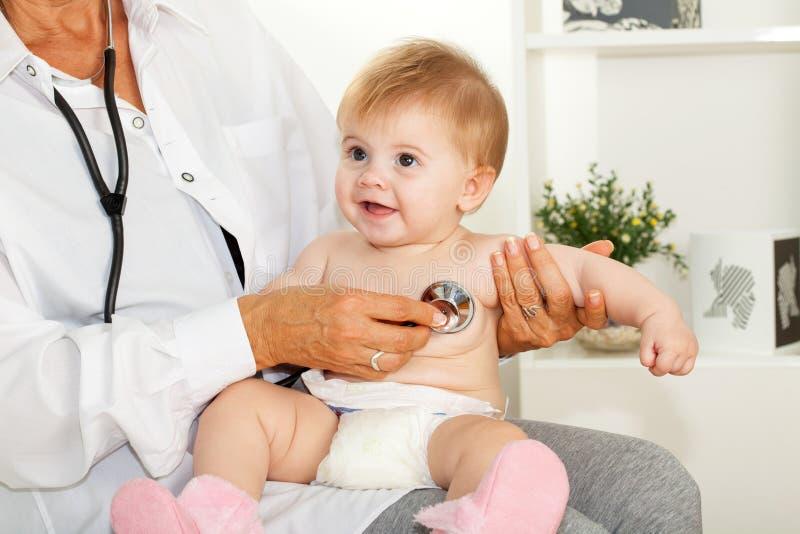 El doctor escucha el corazón del bebé fotos de archivo libres de regalías