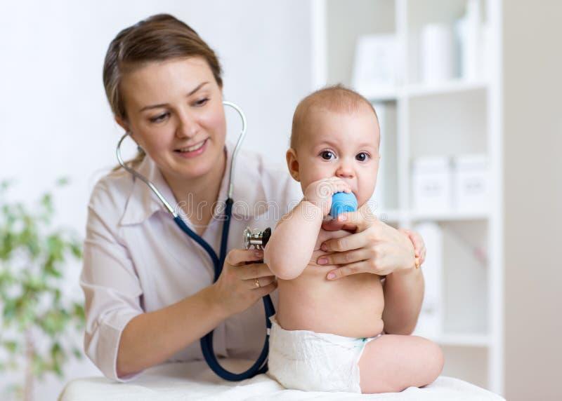 El doctor escucha el corazón del bebé con el estetoscopio foto de archivo
