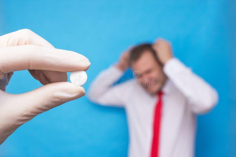 El doctor está sosteniendo una píldora para la psicosis, en el fondo es un hombre que tiene un trastorno mental, psicosis fotos de archivo
