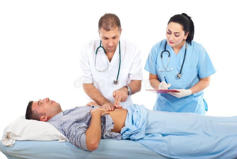 El doctor examina al paciente en cama de hospital imagenes de archivo
