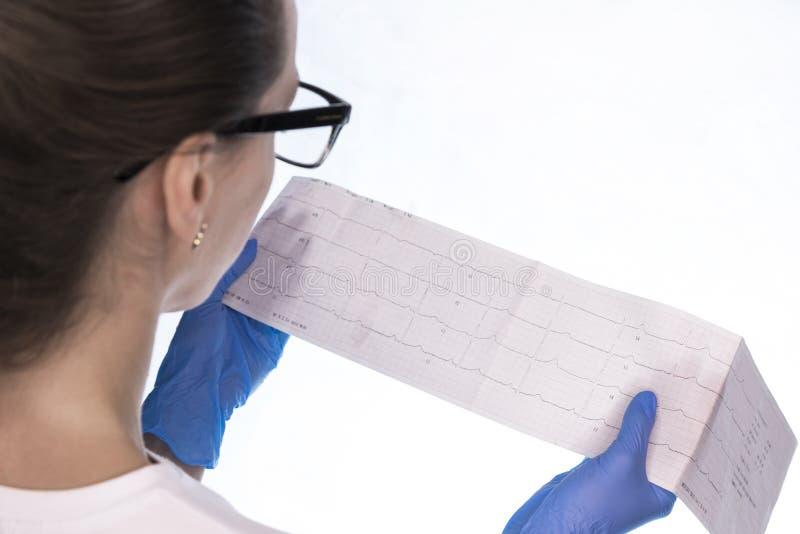 El doctor examina el cardiograma del paciente imagenes de archivo