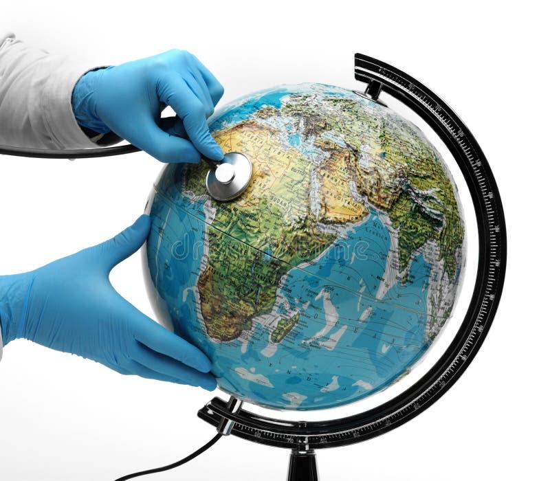 El doctor examina con el stetoscope la tierra enferma foto de archivo