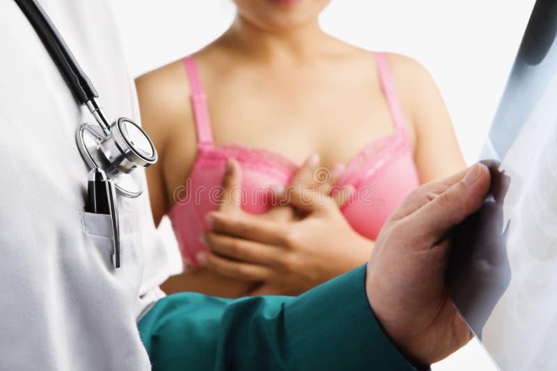 El doctor examina la diapositiva de la radiografía con la mujer en sujetador rosado imagen de archivo libre de regalías