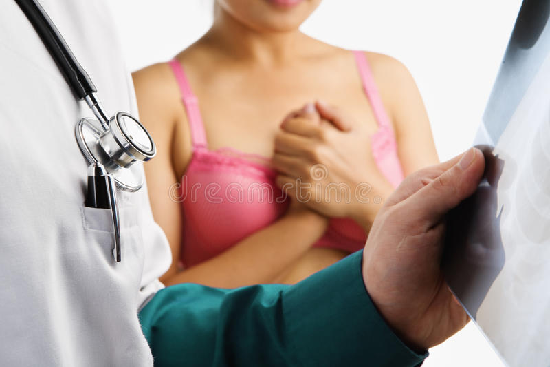 El doctor examina la diapositiva de la radiografía y a la mujer nerviosa imagen de archivo libre de regalías