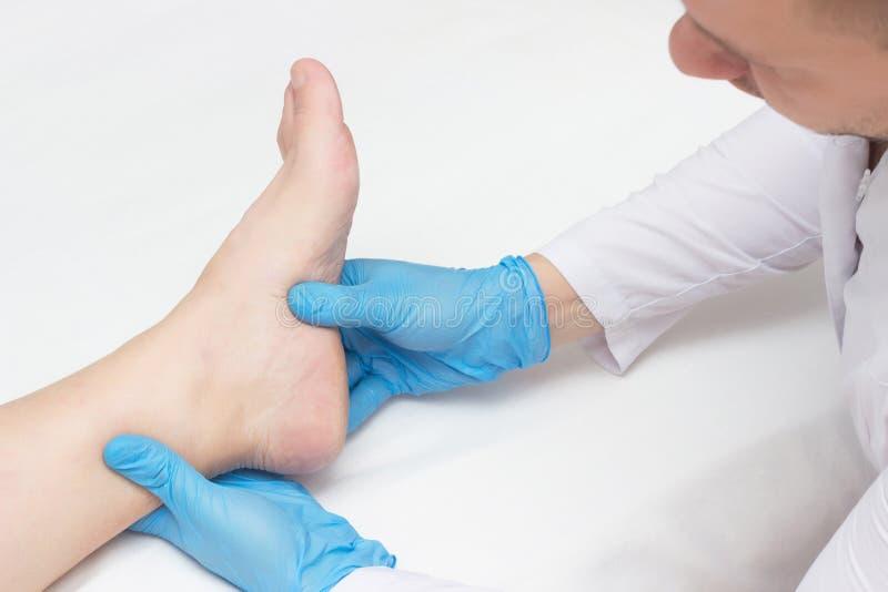 El doctor examina la pierna con los estímulos del talón, dolor en el pie, fondo blanco, primer, fasciitis plantar del paciente fotografía de archivo libre de regalías