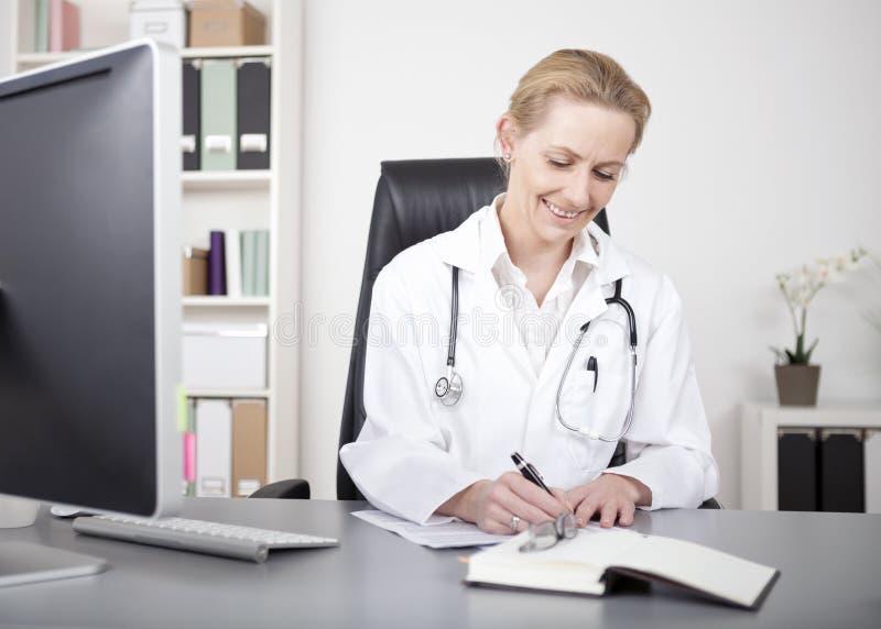 El doctor feliz Making Medical Reports de la mujer en la tabla foto de archivo
