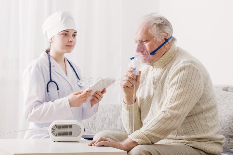 El doctor hace al hombre de los ancianos de la inhalación imagen de archivo