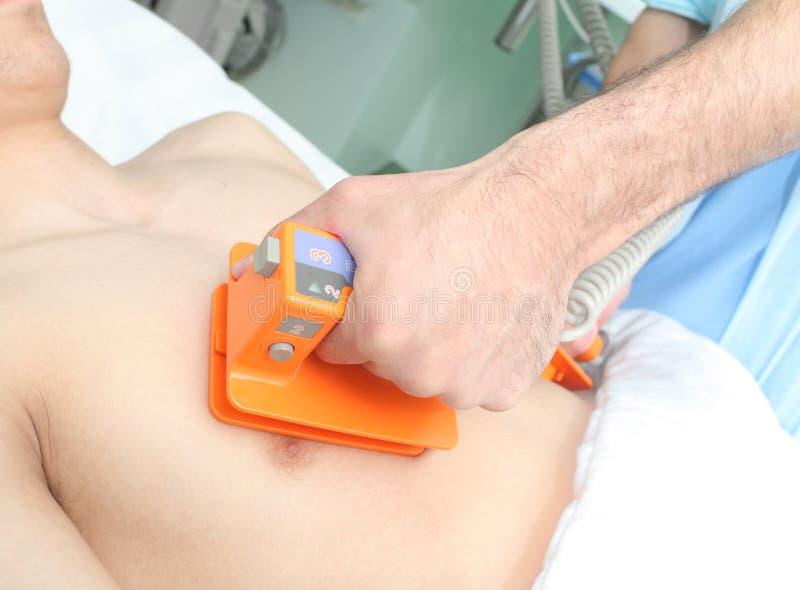 El doctor hace el paciente una desfibrilación eléctrica imagen de archivo