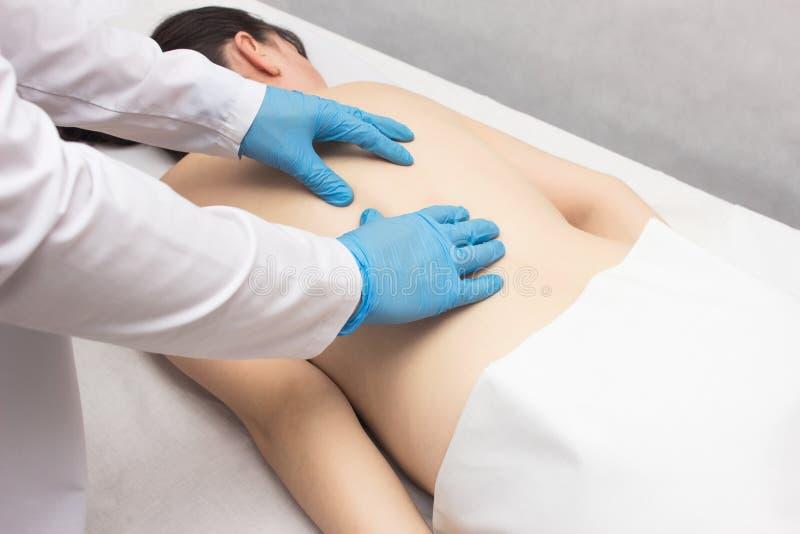 El doctor hace masaje terapéutico a un paciente que tenga problemas y dolor de espalda, médico fotos de archivo