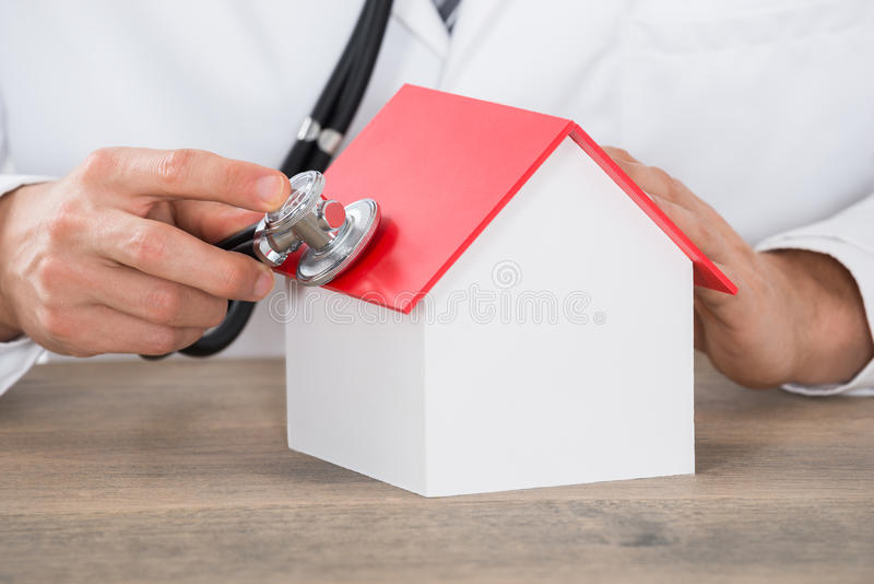El doctor Hand Holding Stethoscope en modelo de la casa fotografía de archivo