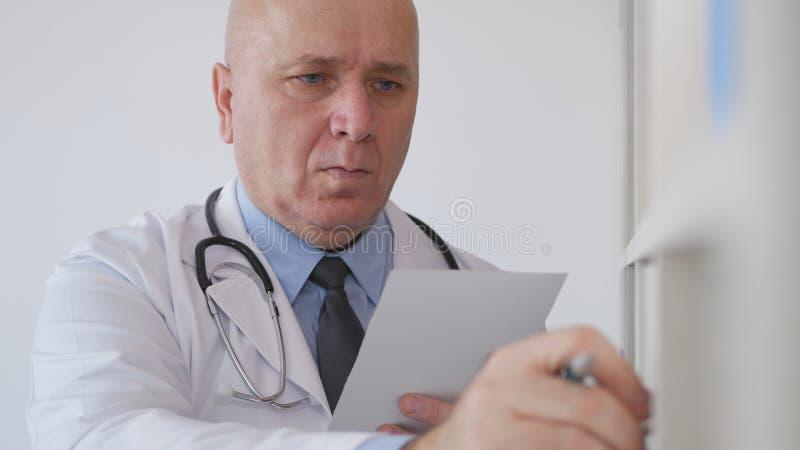 El doctor Image en oficina del hospital abre un cajón con los informes médicos imagen de archivo