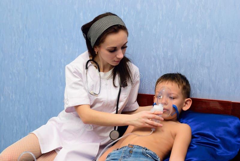 El doctor inhala al muchacho fotografía de archivo libre de regalías