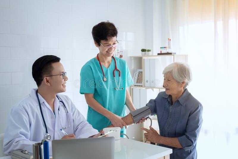 El doctor joven consulta al paciente mayor que se sienta en la oficina del doctor d fotografía de archivo