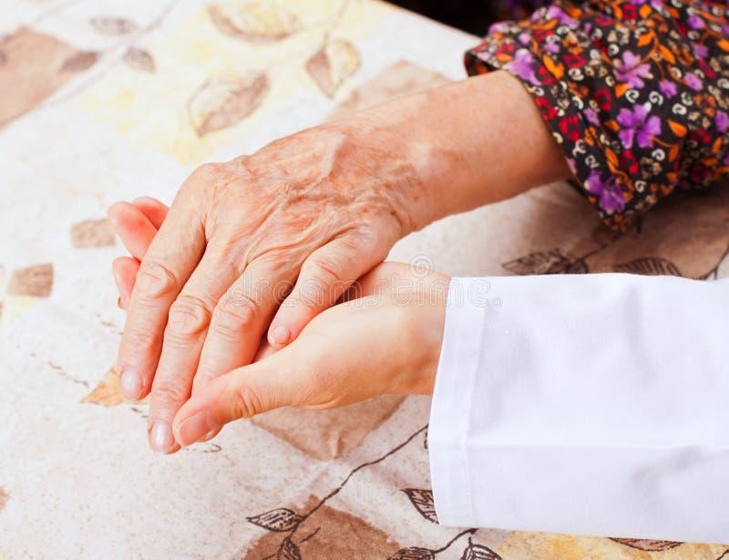 El doctor joven lleva a cabo las manos mayores de la mujer imágenes de archivo libres de regalías