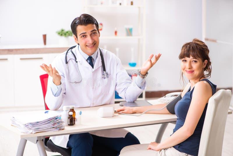 El doctor joven que comprueba la presión arterial de la mujer foto de archivo libre de regalías