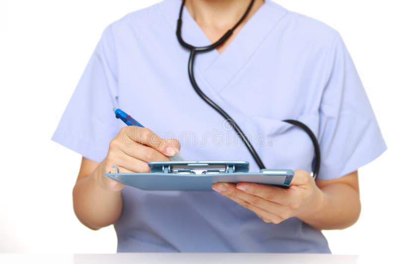 El doctor llena un chart  médico imagenes de archivo