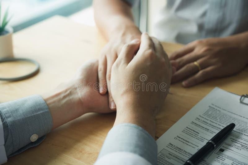 El doctor lleva a cabo las manos y deja confortar a consejeros al paciente fotografía de archivo libre de regalías