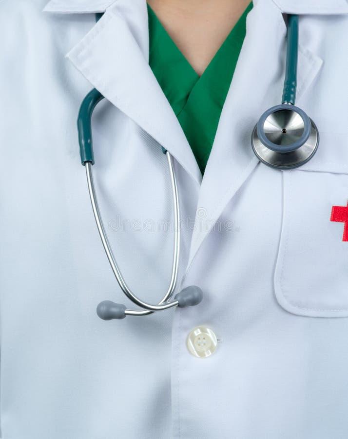 El doctor lleva el uniforme blanco y el verde friega el interior uniforme Doctor con caída del estetoscopio en cuello Profesional imagen de archivo libre de regalías
