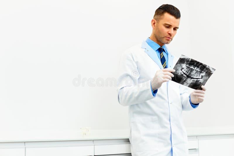 El doctor Looking del dentista en la radiografía en el hospital imagen de archivo