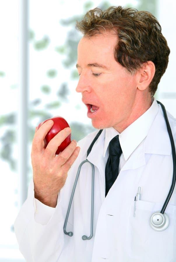 El doctor mayor Eating Red Apple del primer imagen de archivo